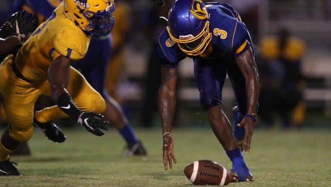 Rickards' Marcus Riley fumbles a snap as Miami Northwestern's Samuel Brooks jr. closes in at Cox Stadium on Saturday, Aug. 19, 2017.