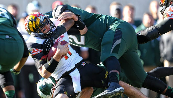 Nov 14, 2015; East Lansing, MI, USA; Maryland Terrapins quarterback Perry Hills (11) is sacked by Michigan State Spartans defensive tackle Craig Evans (72) during the first half at Spartan Stadium.