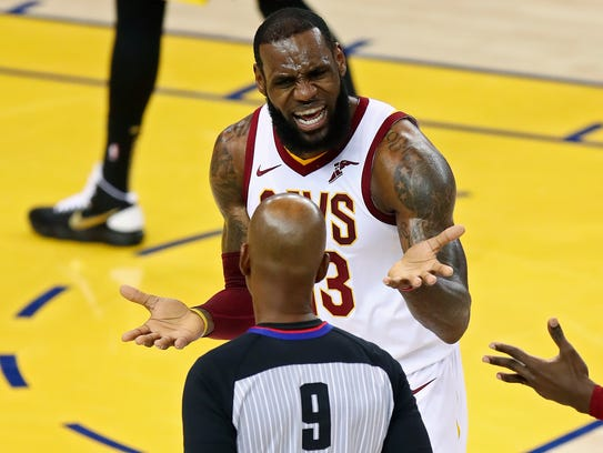 Cleveland Cavaliers forward LeBron James, rear, reacts