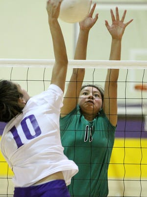 Farmington's JJ Curry goes records a block against Kirland Central's Talia Ockerman on Tuesday at Kirtland Central.