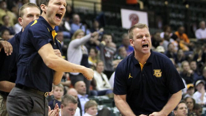 Marquette assistant basketball coach Travis Diener, left, reacts after a big play in a game against Georgia Tech this year.