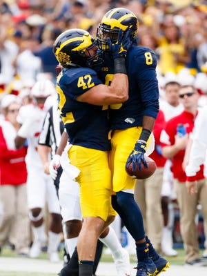 Michigan Wolverines cornerback Channing Stribling (8) receives congratulations from linebacker Ben Gedeon (42) after he makes an interception in the second quarter against the Wisconsin Badgers at Michigan Stadium.