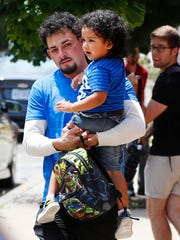 Ever Reyes Mejia, of Honduras, carries his son to a vehicle after being reunited and released by United States Immigration and Customs Enforcement in Grand Rapids, Mich., Tuesday, July 10, 2018. Two boys and a girl who had been in temporary foster care in Grand Rapids, were reunited with their Honduran fathers after they were separated at the U.S.-Mexico border about three months ago.