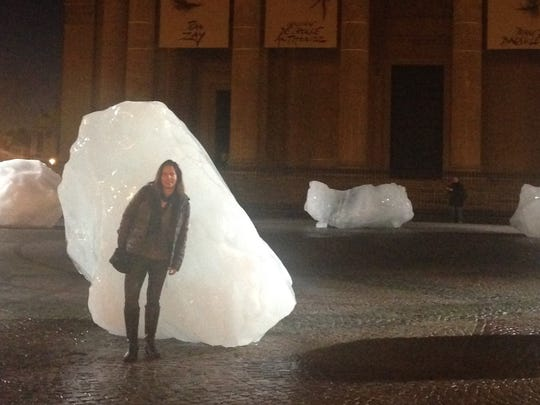 University of Vermont professor Jennie Stephens poses with sculptural blocks of ice from the Greenland ice sheet  in mid-December in Paris. The exhibit was held in conjunction with global climate talks.