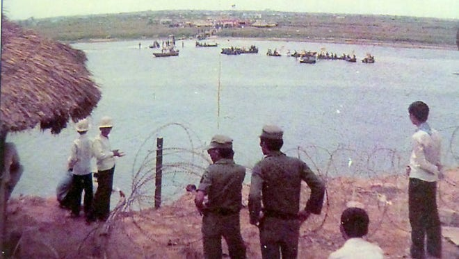 Soldiers watch during a prisoner exchange as POWs cross the river to freedom at Quang Tri. Spencer said by the end of the day, the river was covered with floating shirts from prisoners who tore them off when they knew they had reached a point of safety.