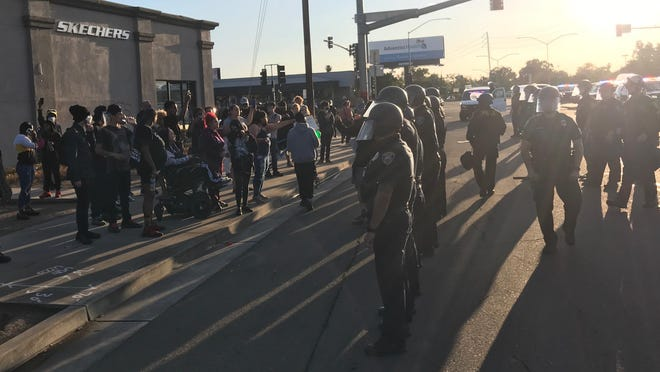 Protesters are moved to the sidewalks at Hammer Lane and Lower Sacramento Road on Friday evening after blocking traffic and shouting at police and passers-by.