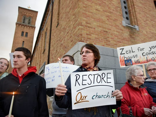 People hold signs to show their support for restoring the Church of St. Mary in Melrose Saturday, April 15, before the start of Easter Vigil ceremonies at the Cathedral of St. Mary in St. Cloud. The Melrose church was heavily damaged by a fire last year.