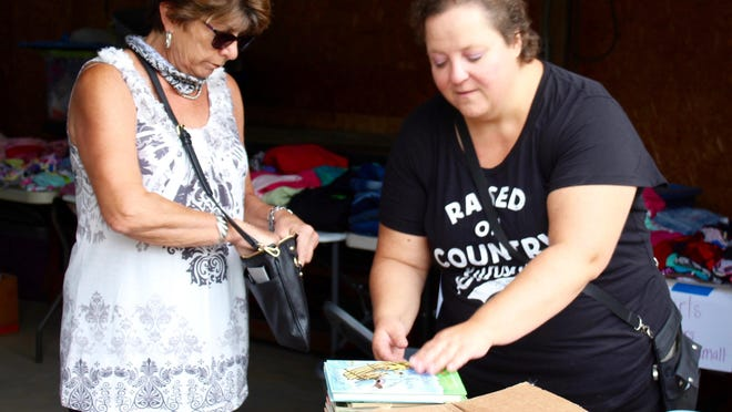 Pam Scrivens of Hillsdale buys books from Heather Wylys Friday in Allen.