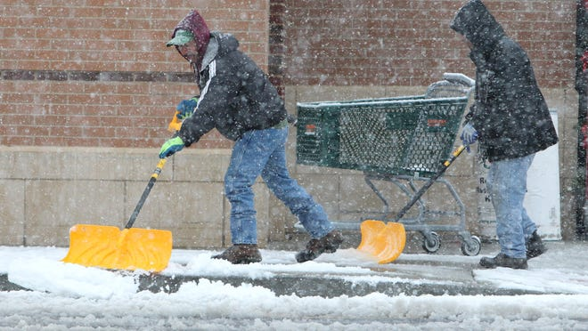 Workers shovel snow at the Fairway Market in Nanuet.