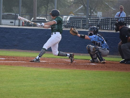 Warrior junior Trevor Saucier makes contact with the ball Tuesday against Barbe.