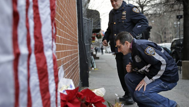 Police officers leave candles at an impromptu memorial Sunday near where two New York City police officers were killed Saturday in Brooklyn. Police say Ismaaiyl Brinsley ambushed officers Rafael Ramos and Wenjian Liu in their patrol car in broad daylight, fatally shooting them before killing himself inside a subway station.