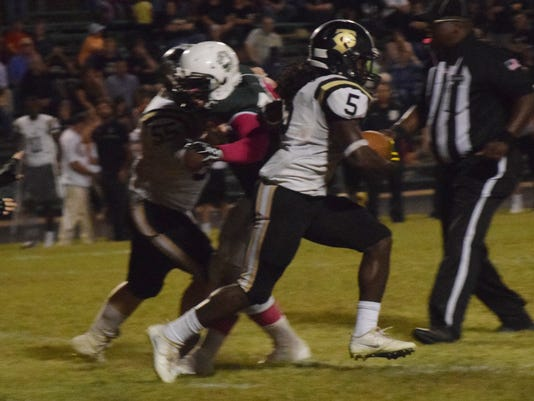 Jena High School's Chico Savage (5) runs through Peabody Magnet High School defenders.