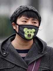 A woman wears a mask outside Tiantan Park in Beijing