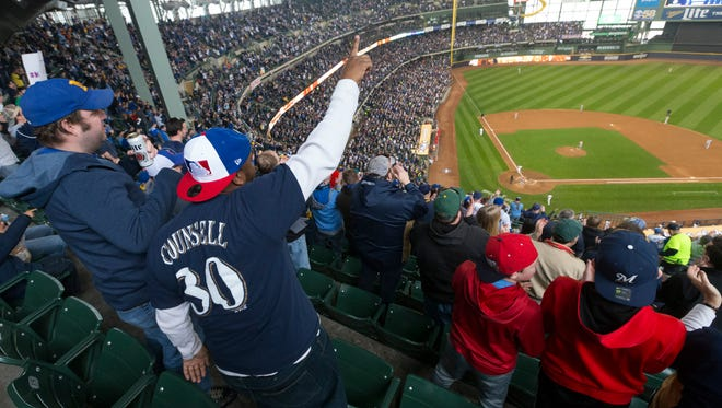 Fans cheer after Milwaukee Brewers Lorenzo Cain hit a home run over the left field wall in the third inning of his team's home opener against the St. Louis Cardinals at Miller Park. MARK HOFFMAN/MILWAUKEE JOURNAL SENTINEL