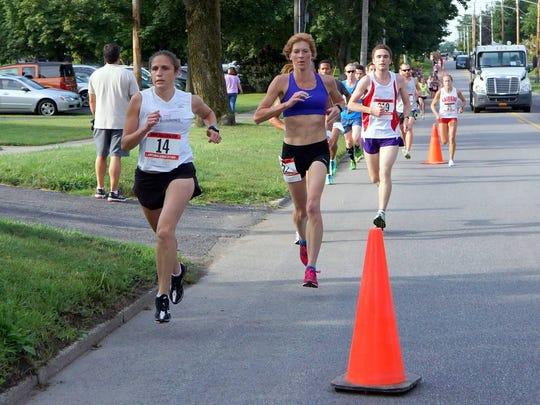 Trisha Byler, front left, and Karen Blodgett, center behind Byler, run the Jenny Kuzma Bergen 5K in Bergen, NY last August. Byler and Blodgett are two-thirds of a trio of women who train together.