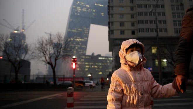 A woman wears a mask on a street shrouded in smog in Beijing, on Dec. 7, 2015.