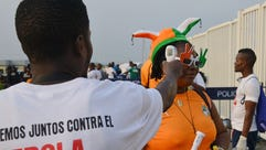 A health worker checks the body temperature of a fan