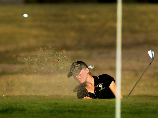 Newbury Park High's Skyler Wood hits out of a bunker to get within a foot of the cup on the third hole during the  CIF-SS Girls Northern Individuals at River Ridge Golf Course in Oxnard Monday. She and her twin sister, Madison, both advanced to the finals.
