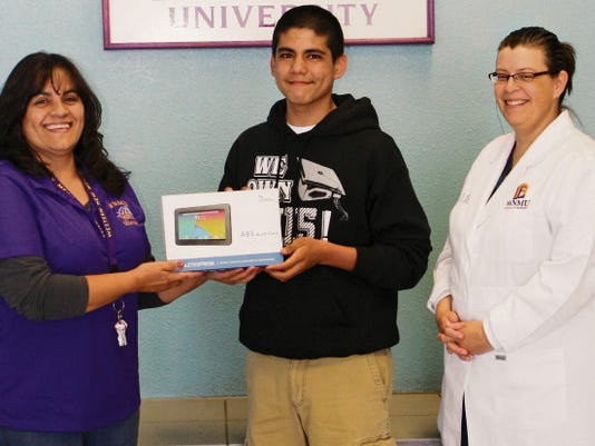 Submitted Photo   Andy Romero, a student at Western New Mexico University-Deming, received a brand new Dragon Tablet from Elizabeth Davila, WNMU-Deming student services specialist while Sasha Poole, site coordinator for the nursing program looks on. Poole chose the winning entry from a group of 20  WNMU-Deming students who attended the school's Fall 2015 registration blitz held from 3-8 p.m. on April 14, at the Mimbres Valley Learning Center, 2300 E. Pine St.
