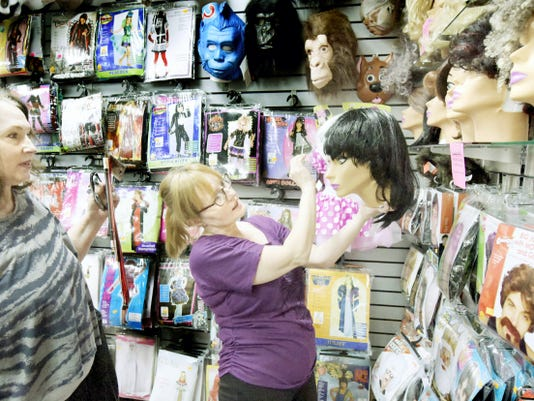 Make Believin' owner Debbi Reck shows a Cruella De Vil wig to Tiann Scoggins, left, of Spring Garden Township, who was shopping for her neice's costume at the York Township costume shop Tuesday, Oct. 13, 2015. Bill Kalina - bkalina@yorkdispatch.com