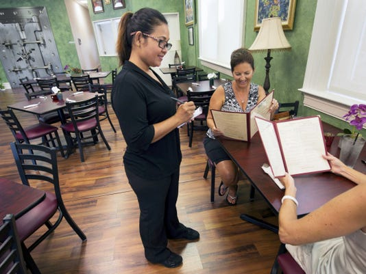From the left, Yui Markle takes an order from Beth Smith, of York Township, and Cindy Friedrich, of Springfield Township at Krua Thai Cafe.