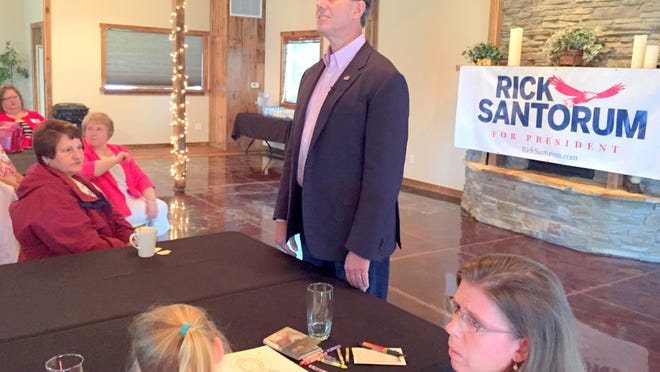 Rick Santorum leans to listen to a question Thursday during a town hall meeting at the Wooden Wheel Vineyards near Keota, Iowa.