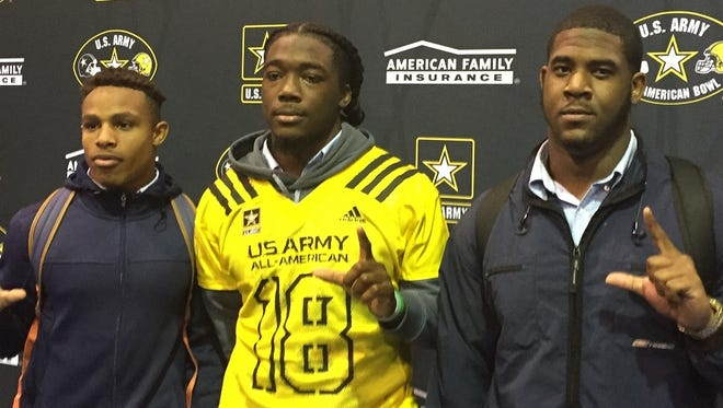 Flanked by fellow LSU commits Ar'Darius Washington and Davin Cotton,  Evangel's Micah Baskerville displays his U.S. Army All-American Bowl  jersey.