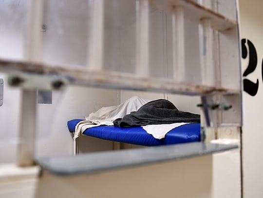 An inmate is covered in blankets in a cell in the mental
