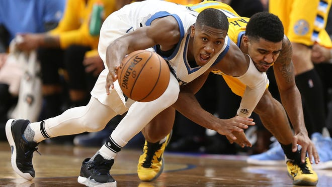 Minnesota Timberwolves guard Kris Dunn (3) tries to grab a lose ball against Denver Nuggets guard Gary Harris, right, in the first half of an NBA basketball game, Sunday, Jan. 22, 2017, in Minneapolis.
