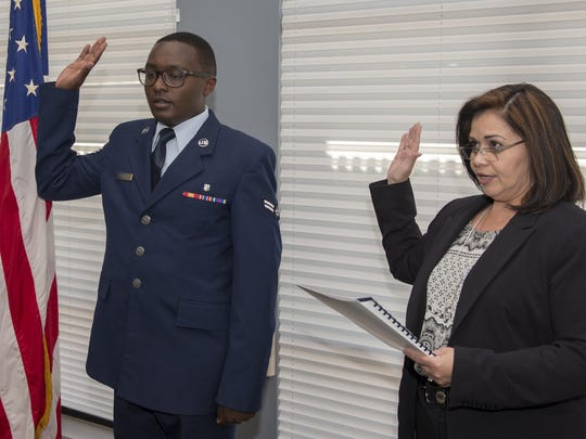 Airman 1st Class Samuel Kamau, a 49th Medical Group dental technician here, swears the Oath of Allegiance being administered by Margaret Hartnett, a Department of Homeland Security officer, inside the dental clinic here April 14. Originally from Kenya, Africa, Kamau joined the Air Force to become a U.S. citizen and for the educational opportunities.