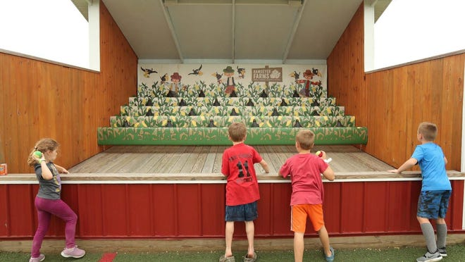Children attempt to throw balls at crow targets to make them cackle at Ramseyer Farms Friday, Sept. 11, 2020 in Wooster, Ohio.