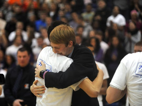 Zanesville High School senior Eric Walker gets a hug from a teammate as he is introduced on Senior Night before Monday night's basketball game. Eric is battling cancer, and the district has rallied in support.