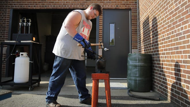 Brandon Kluba, a senior at Appleton Technical Academy, uses a hammer and anvil along with a portable forge to create a set of tongs that will be used for the forge in the future on Sept. 25 in Appleton. The academy is located at Appleton West High School.