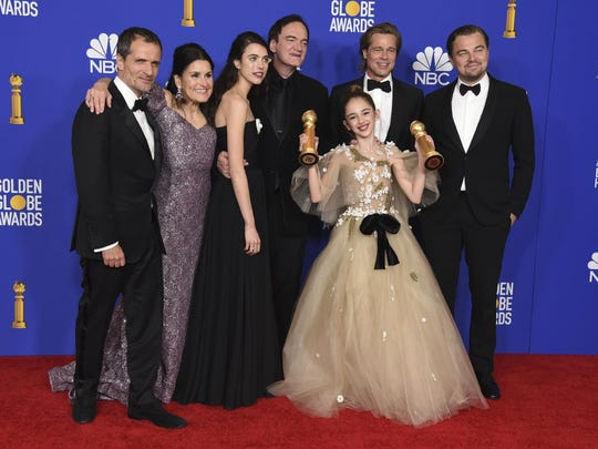 """The cast and crew of """"Once Upon a Time in Hollywood"""" pose in the press room with the awards for best motion picture, musical or comedy and best screenplay, motion picture, Sunday at the 77th annual Golden Globe Awards."""