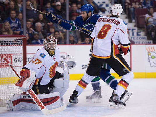 Calgary Flames center Joe Colborne (8) tries to clear Vancouver Canucks right wing Zack Kassian from in front of Flames goalie Joni Ortio (37) during the first period of an NHL hockey game Saturday, Jan. 10, 2015, in Vancouver, British Columbia. (AP Photo/The Canadian Press, Jonathan Hayward)