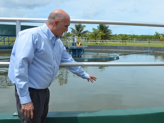 In this September 2013 file photo, Martin Roush, left, former Guam Waterworks Authority general manager, explains how wastewater is treated at the Northern Wastewater Treatment plant. The water agency spent $10 million to allow the plant to give primary treatment to sewage, which had been pumped out to sea, untreated. A new $120 million contract to Black Construction will add a secondary treatment process at the plant.