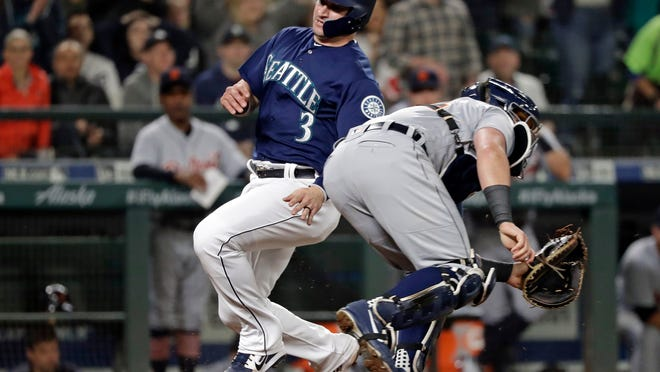 Mike Zunino slides safely into home as James McCann waits for the throw in the seventh inning Friday in Seattle.