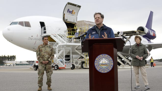 Gov. Chris Sununu, center, speaks to reporters as N.H. National Guard Maj. Gen. David Mikolaities, left, and Sen. Jeanne Shaheen, D-N.H., right, look on as pallets containing personal protective equipment, behind, are unloaded from a FedEx cargo plane, April 12, 2020, at Manchester-Boston Regional Airport.