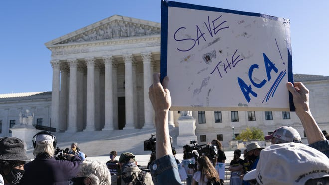 A demonstrator holds a sign in front of the U.S. Supreme Court as arguments are heard about the Affordable Care Act Tuesday, Nov. 10, 2020, in Washington.
