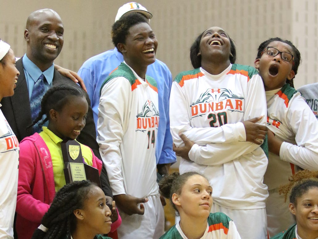 Dunbar celebrates during the trophy ceremony following the ladies basketball game at Dunbar High School in Fort Myers, FL on Wednesday, January 27, 2016. Dunbar defeated Cypress Lake to win the District 12 Championship.
