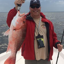 Pensacola Beach resident Bill Schwartz shows off a big red snapper he landed while fishing in Pensacola Bay earlier this year.
