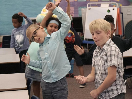 """Students in the second-grade multicultural class dance to Earth, Wind and Fire's """"Shining Star."""" Teacher Misuk Drews explained that this will be the class's theme for the year."""