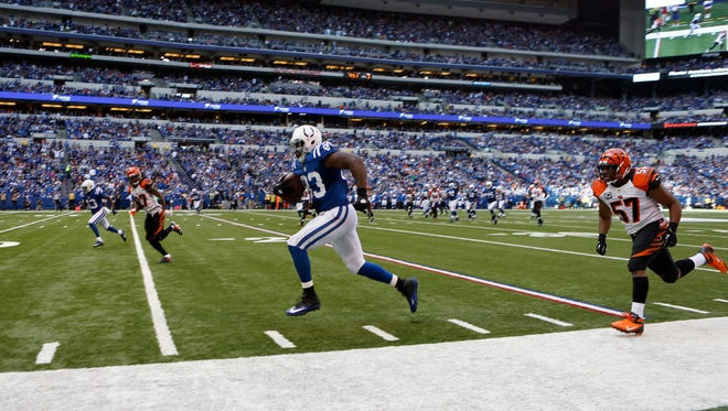 Sunday, Oct. 19, 2014 BENGALS SPORTS :  Indianapolis Colts tight end Dwayne Allen (83) runs for a touchdown after a reception in the third quarter past the Cincinnati Bengals outside linebacker Vincent Rey (57)at Lucas Oil Stadium.  The Enquirer/Jeff Swinger