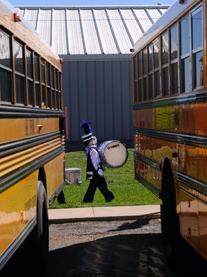 Hartley Sager, 13, walks past the school buses with her bass drum as she and the rest of the Roscoe Collegiate High School Big Purple Band ready themselves to take the field. Twenty-one high school marching bands performed Monday Oct. 16, 2017 at Wylie High School during the Big Country Marching Festival.