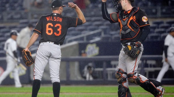 Baltimore Orioles starting pitcher Tyler Wilson (63) high-fives catcher Matt Wieters after they defeatedthe New York Yankees in a baseball game, Friday, Sept. 30, 2016, in New York. (AP Photo/Julie Jacobson)