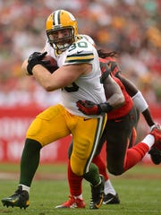 Green Bay Packers fullback John Kuhn (30) tries to elude Tampa Bay Buccaneers linebacker Danny Lansanah (51) while making a run in the fourth quarter during Sunday's game at Raymond James Stadium in Tampa, Fla.