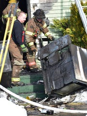 Scorched appliances are removed following a house fire
