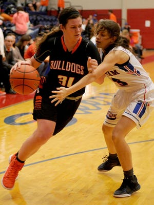 Burkburnett's Kaci Trahan drives to the basket while guarded by Graham's Michelle Delong Friday, Feb. 3, 2017, in Graham. The Lady Bulldogs defeated the Lady Blues 56-35.