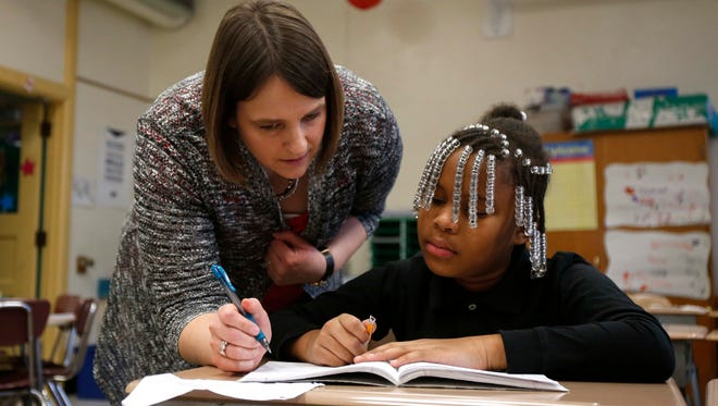 Katie Rieck, a third grade teacher at Moulton Elementary School in Des Moines, helps Barbrianna Dantzler on a problem during class on Thursday, March 3, 2016.