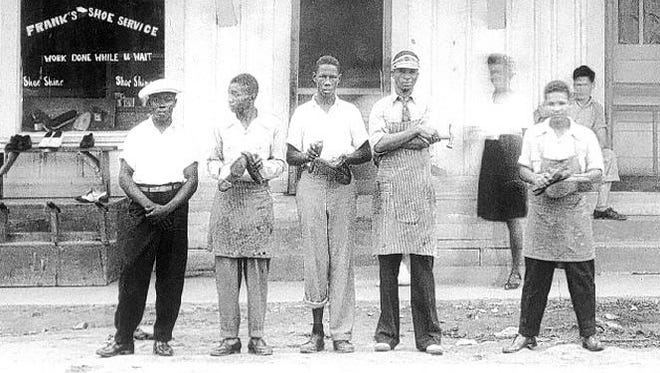 Frank Morris (second from left, wearing visor) stands in front of his Ferriday shoe repair business.